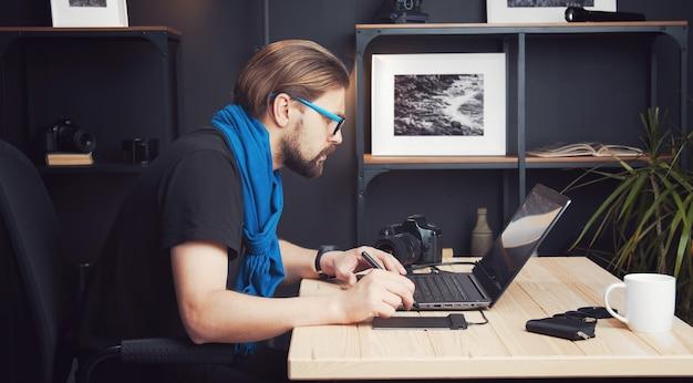 Seitenansicht des professionellen fotografen, der bilder retuschiert, die in der fotobearbeitungsanwendung arbeiten