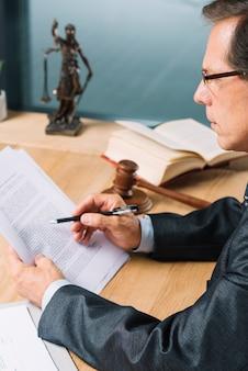 Seitenansicht des reifen männlichen rechtsanwaltlesedokuments im gerichtssaal