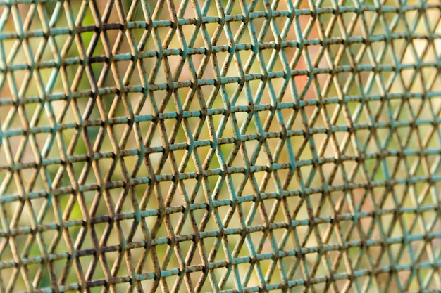 Seitenansicht des rostigen käfigs. grüner hintergrund