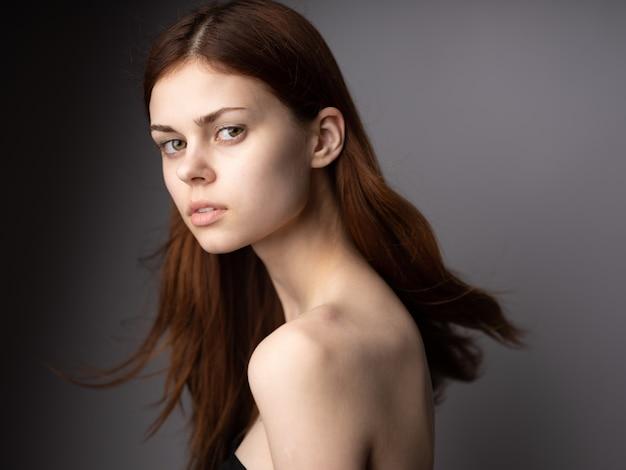 Seitenansicht des rothaarigen frauenporträts auf grauem schönem gesicht