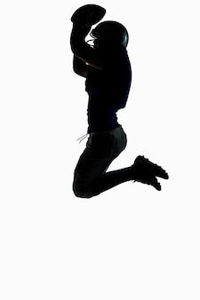 Seitenansicht des schattenbildes spieler des amerikanischen fußballs, der beim halten des balls gegen weißen hintergrund springt