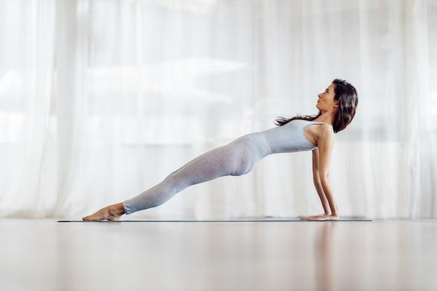 Seitenansicht des schlanken flexiblen mädchens mit langen haaren in der aufwärtsplanken-yoga-position. yoga studio interieur.