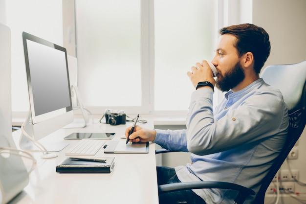 Seitenansicht des schönen bärtigen mannes, der frisches heißes getränk genießt und moderne grafische tablette verwendet, während im büro arbeitet. männlicher designer, der heißes getränk trinkt und zeichnungstafel verwendet