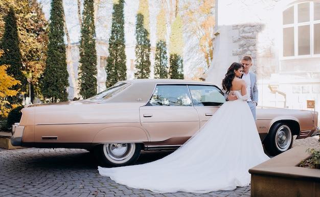 Seitenansicht des schönen brautpaares steht an einem sonnigen tag auf dem hintergrund eines rosa autos