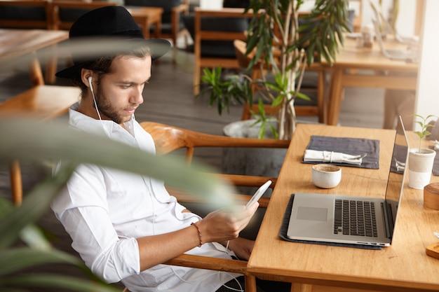 Seitenansicht des schönen jungen kaukasischen freiberuflers oder studenten, der am kaffeetisch mit offenem laptop-pc sitzt, handy hält und musik auf kopfhörern hört, unter verwendung der online-app während des frühstücks