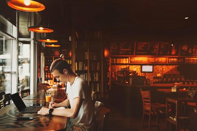 Seitenansicht des schönen jungen mannes in der freizeitkleidung mit kreativem haarschnitt, der am fenstertisch in den kopfhörern mit laptop sitzt und in notizblock in bar schreibt