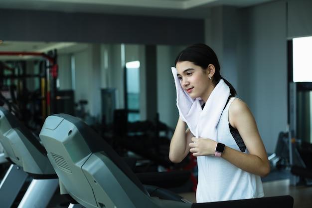 Seitenansicht des schönen mädchens, das auf laufband im fitnessstudio läuft