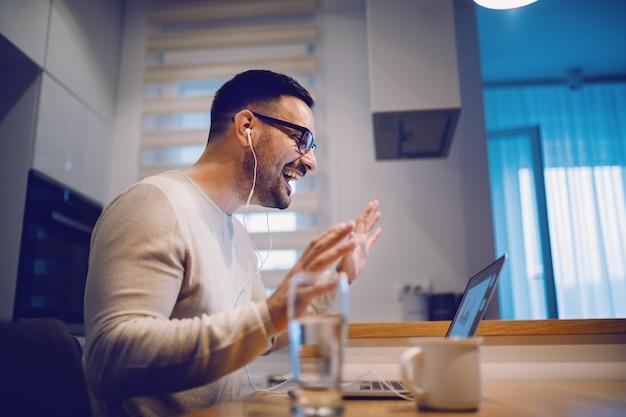 Seitenansicht des schönen positiven mannes gekleidet lässig sitzend am esstisch in der küche und mit videoanruf über laptop mit seiner freundin. auf dem tisch neben dem laptop stehen ein glas wasser und kaffee.