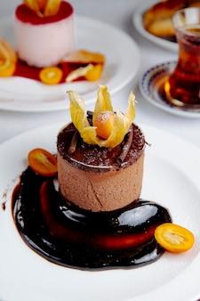 Seitenansicht des schokoladenkäsekuchens, der mit kumquat gekrönt wird