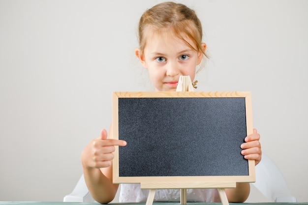 Seitenansicht des schulkonzepts. kleines mädchen hält und zeigt tafel.
