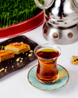 Seitenansicht des schwarzen tees im armudu-glas mit pakhlava