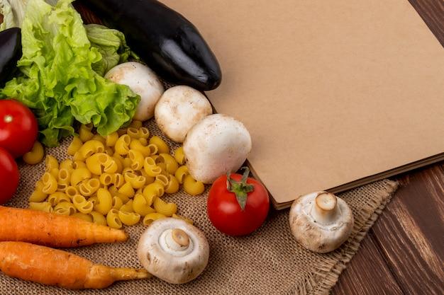 Seitenansicht des skizzenbuchs und der rohen nudeln mit champignon-karotten-tomaten-auberginen und -salat der frischen pilze auf sackleinen auf hölzernem hintergrund Kostenlose Fotos