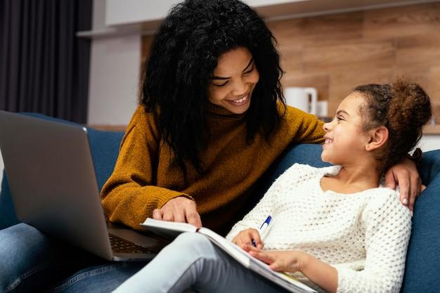 Seitenansicht des smiley-mädchens, das kleine schwester mit online-schule hilft