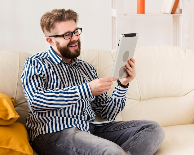 Seitenansicht des smiley-mannes auf sofa mit tablette