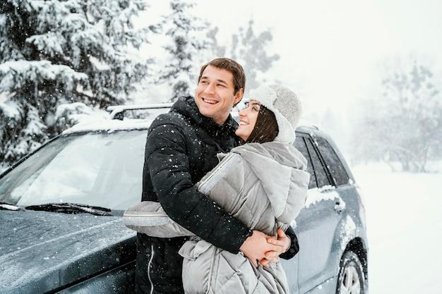 Seitenansicht des smiley-paares, das im schnee umarmt, während auf einem roadtrip