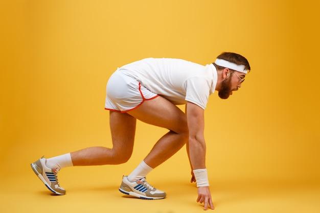 Seitenansicht des sportlers in der sonnenbrille, die sich zum laufen vorbereitet