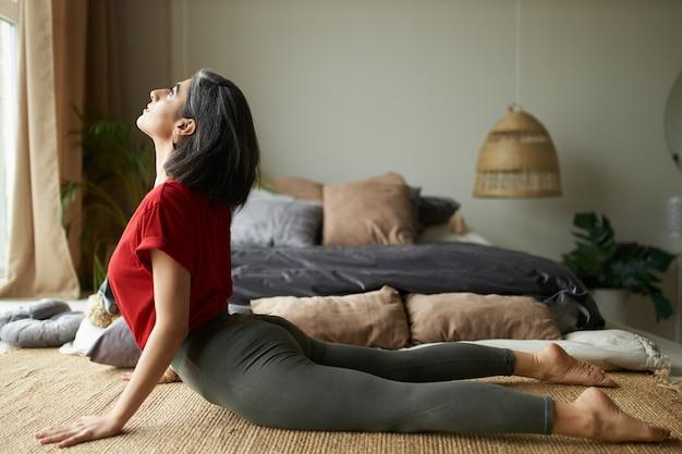 Seitenansicht des sportlichen barfußmädchens mit starkem flexiblem körper, der zu hause trainiert