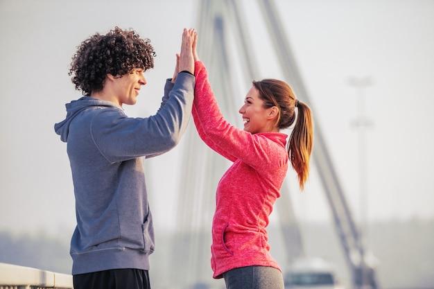 Seitenansicht des sportlichen kaukasischen paares, das einander hohe fünf gibt, während auf der brücke bei kaltem wetter steht. outdoor-fitness-konzept.