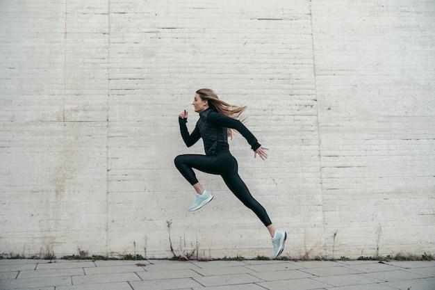 Seitenansicht des springens der jungen sportlerin