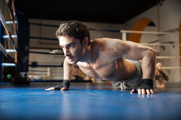 Seitenansicht des starken boxers, der liegestütze tut