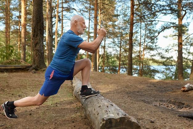 Seitenansicht des starken passenden älteren mannes mit bart, der im wald ausarbeitet, doig ausfallschritte, füße auf protokoll halten. konzentrierter älterer mann, der körperliche übungen für beinmuskeln am sonnigen sommertag tut