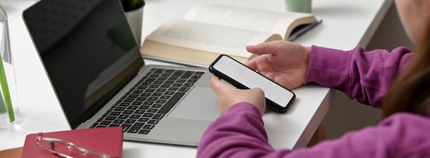Seitenansicht des studenten, der nach informationen auf modell-smartphone sucht