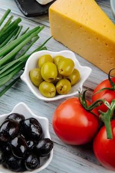 Seitenansicht des stückes holländischen käses mit frühlingszwiebeln, eingelegten oliven und frischen tomaten auf grauem holztisch