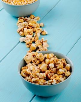 Seitenansicht des süßen karamellpopcorns in einer schüssel auf blauem hintergrund