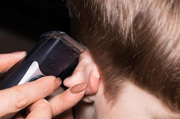 Seitenansicht des süßen kleinen jungen, der vom friseur im friseursalon mit kamm und pflegeschere einen haarschnitt erhält. nahaufnahme.