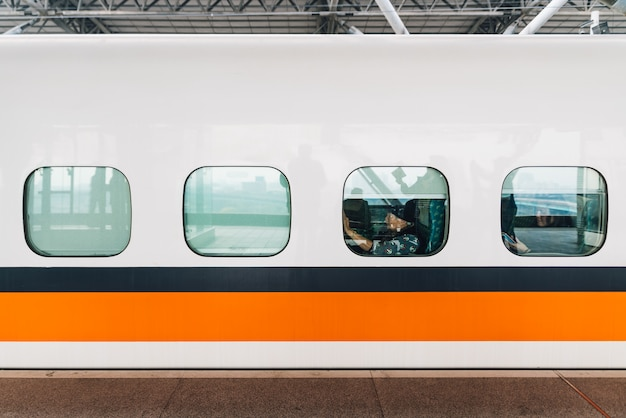 Seitenansicht des taiwan-hochgeschwindigkeitszugs, weißer zug mit orange und blauem streifen.