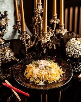 Seitenansicht des thunfischsalats mit käse und wachteleiern auf einem teller auf schwarzem teller