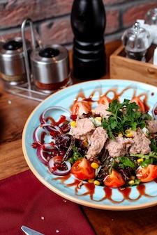 Seitenansicht des thunfischsalats mit roten zwiebeln und tomaten auf einem teller