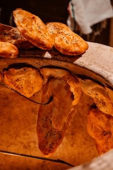Seitenansicht des traditionellen aserbaidschanischen tandoor-brotes, das in einem lehmofen gebacken wird, der tandoor genannt wird