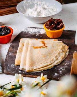 Seitenansicht des traditionellen russischen frühstückspfannkuchens mit marmeladensauce und milch auf einem hölzernen schneidebrett