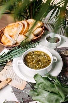 Seitenansicht des traditionellen russischen grünen borschtsches mit sauerampferfleisch und von eiern auf einem holzbrett