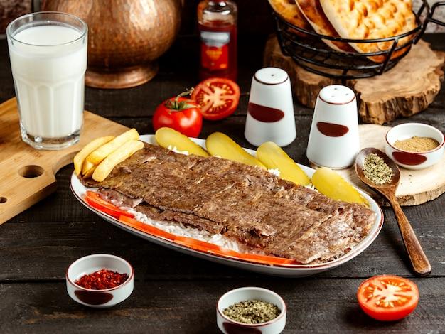 Seitenansicht des traditionellen türkischen kebab-ikenders auf reis mit gurken auf platte