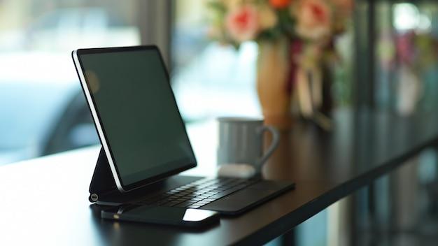 Seitenansicht des tragbaren arbeitsbereichs mit digitalem tablet und smartphone auf schwarzem schreibtisch