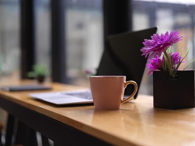 Seitenansicht des tragbaren arbeitsbereichs mit laptop, getränkebecher und blumenvase auf bar im café