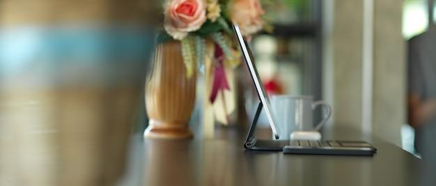 Seitenansicht des tragbaren arbeitsbereichs mit tablette, smartphone und blumenvase verziert auf dem tisch