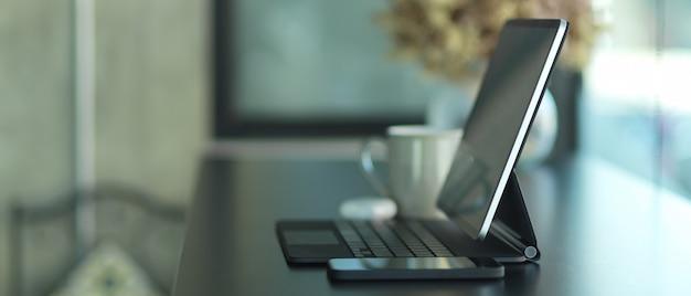 Seitenansicht des tragbaren arbeitsbereichs mit tablette, smartphone und dekorationen im café