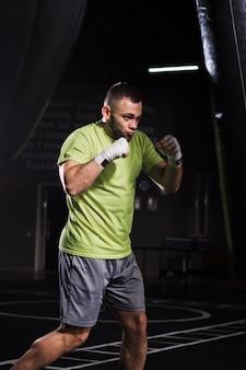 Seitenansicht des tragenden t-shirts und der kurzen hosen des männlichen boxers, die mit sandsack üben