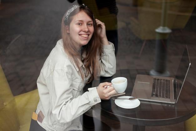 Seitenansicht des trinkenden kaffees der glücklichen frau