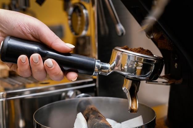 Seitenansicht des weiblichen barista unter verwendung der professionellen kaffeemaschine