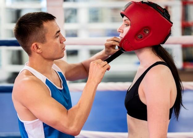 Seitenansicht des weiblichen boxers, der für den ring bereit macht