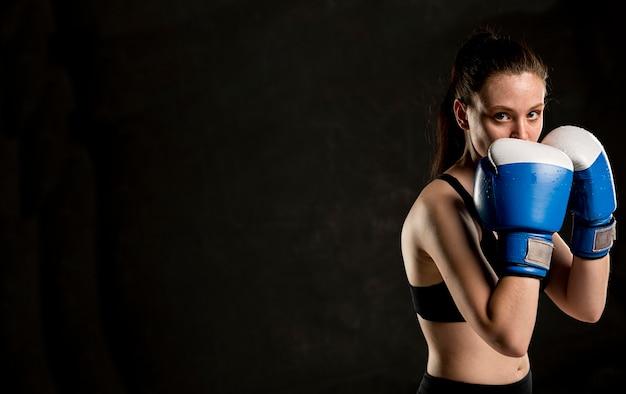 Seitenansicht des weiblichen boxers, der mit kopienraum aufwirft