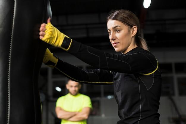 Seitenansicht des weiblichen boxers mit defocused trainer