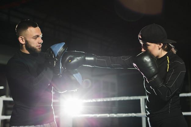 Seitenansicht des weiblichen boxers übend im ring mit trainer