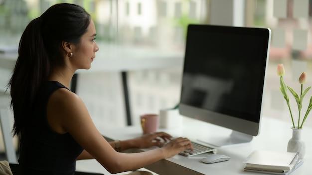 Seitenansicht des weiblichen büroangestellten, der mit computer auf arbeitstisch mit vorräten und blumenvase arbeitet
