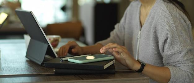 Seitenansicht des weiblichen freiberuflers, der mit digitalem tablett, laptop und smartphone auf holztisch arbeitet