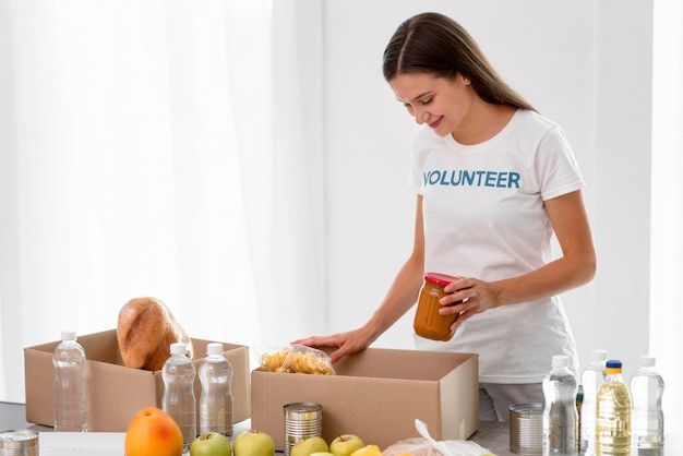 Seitenansicht des weiblichen freiwilligen, der lebensmittel in kisten für spende verpackt